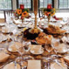 Fall theme décor with orange, yellow & red floral centerpieces