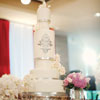Six tier white cake with silver ribbon detail, silver stencilling and pale pink roses