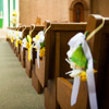Small yellow and white floral bouquets tied to church pews in matching ribbon