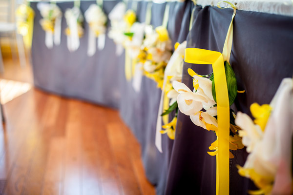 White and yellow flower bundles with matching ribbons hanging from reception tables