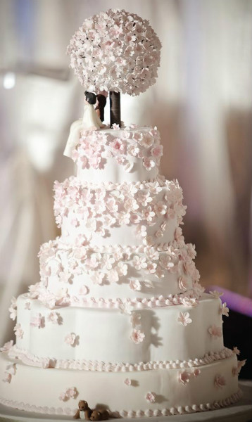 Five tier cake with pink cherry blossom bouquet topper and cherry blossom petal detail