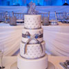 4 tier white cake with silver stud detailing, lavender ribbons and glass cake topper