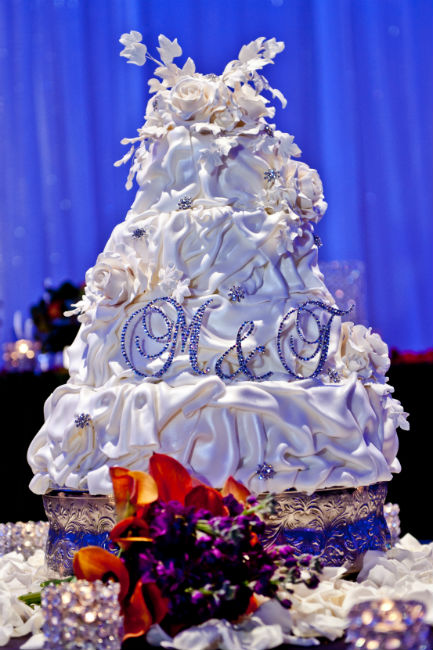 Whimsical floral three tiered ruffled fondant cake with sequin monogram initial topper
