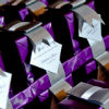 Small box favours with metallic purple wrapping, personalized message and silver bows