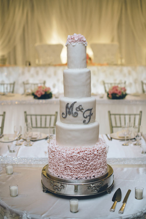 5 tier white cake with silver initials and pink ruffled bottom