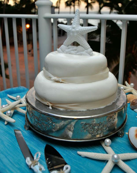 Nautical theme two tier cake with white starfish and seashell topper