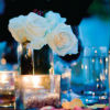 White rose centerpieces, wine bottles and pink flower petal accents