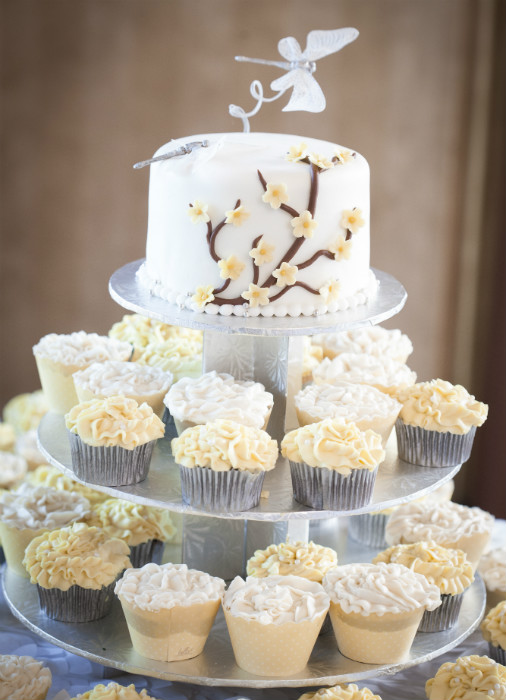 Four tier white and yellow cupcake tower with a full white cake top tier with butterfly topper and yellow cherry blossom fondant