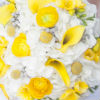 Fresh summer bouquet of yellow roses and calla lillies, white daisies, and additional white floral accents