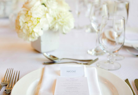 All white linens, place setting and floral centerpiece