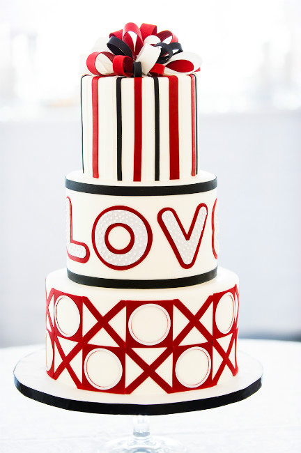 Modern three tier red, black and white cake with fondant LOVE, X's and O's and present bow accents