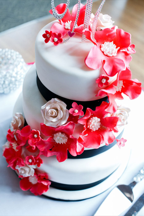 White three tier cake with black fondant ribbon trim, red and cream floral accents and monogram crystal topper