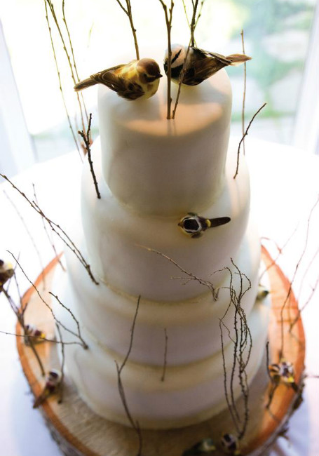 Whimsical white outdoor cake with thin branches and songbird topper