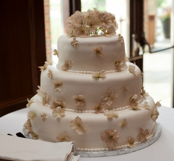 Outdoor-inspired three tier white cake with tan flower accents and piped icing trim.