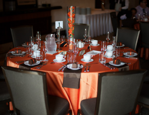 Elegant table decor with draping chocolate brown napkins and burnt orange accents