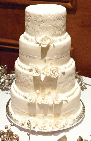 Romantic four tier all white cake with embossed stenciling