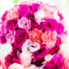 Vibrant pink pomander bouquet surrounded by pink and white roses and carnations