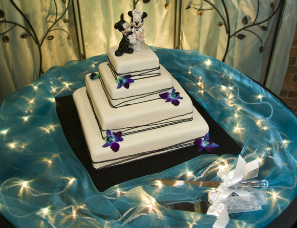 Elegant four-tiered square cake with Mickey and Minnie topper