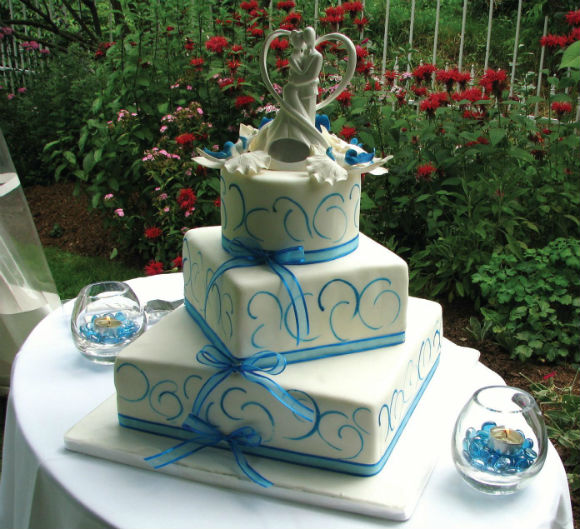White & blue three tier cake with sheer blue ribbon trim & couple silhouette topper