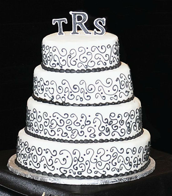 Black and white four tier cake with black buttercream design and monogram inital toppers