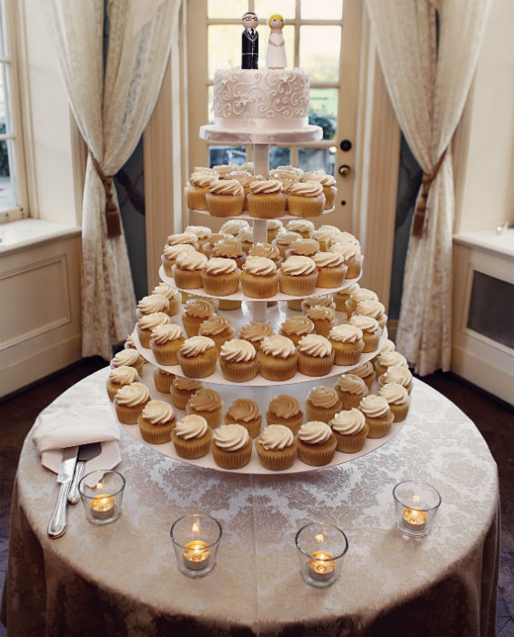 Five tier cupcake cake with metallic mini cake top layer with piped accents and groom and bride toppers.