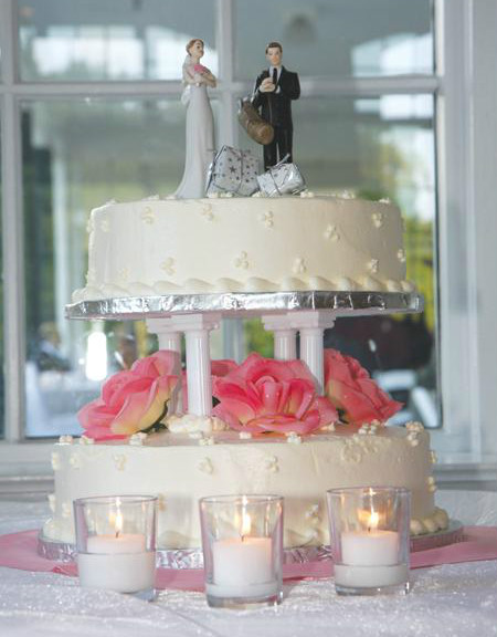 Elegant white two tier cake with open pink roses and bride and groom figurine topper