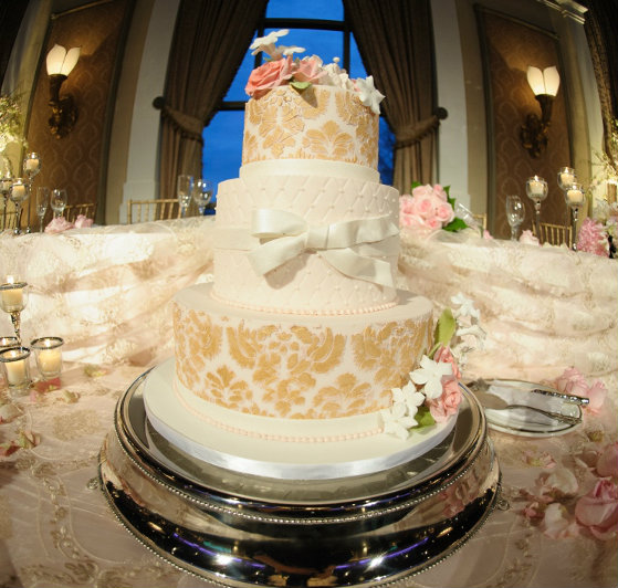 Three-tier ivory cake with gold stencil accents and a quilted fondant middle tier with a white fondant bow