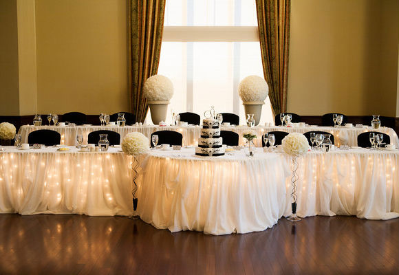 Double Head Table With Black Chairs, White Floral Accents And White Linens  And Place Settings