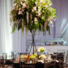 Large white and green floral arrangement on top of a sleek black tripod