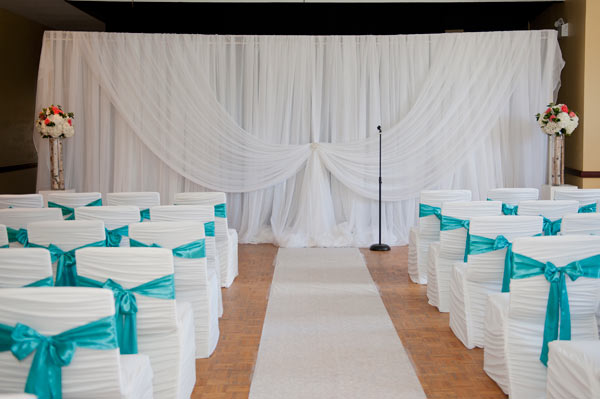 Ceremony backdrop with matching decorated chairs with turquoise sash
