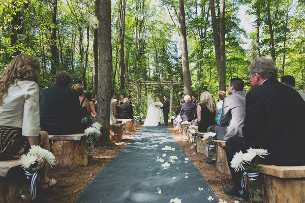 Outdoor Aisle With Grey Runner And Tree Trunk Benches Adorned White Carnation Bouquets