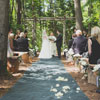 Outdoor aisle with grey runner and tree trunk benches adorned with white carnation bouquets
