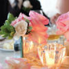 Pink and white flower table accents with candles and flower petals