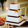 Three tier white cake with black chocolate ribbon detail and autumn flowers