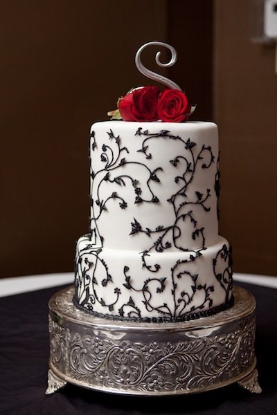 White two tier cake with silver metal base, black vine accents and red rose topper