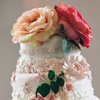 Four tier cake with white and pink floral icing accents and large peach and coral flower topper