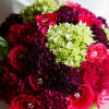 Bright coloured bouquet with pink and mauve carnations, fuchsia roses, green flowers and jeweled accents.