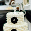 Three tier white cake with woven icing, clear bead trim, black floral accents and metal heart topper