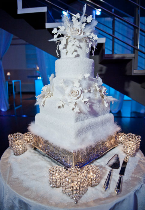 Five tier white cake with embossed metallic base and floral and feather accents and topper