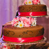 Five single tier chocolate brown cakes on pedestals of varying height with pink trim and white and pink floral accents