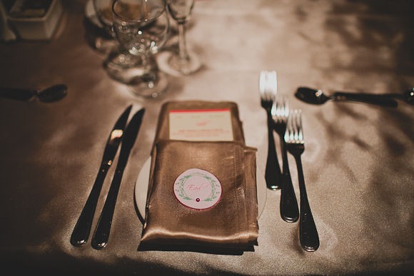 Gold napkin with guest table setting against white table linens