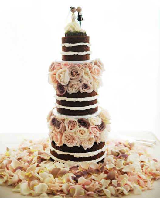 Three tier, nine layer chocolate cake with white icing, pastel rose accents and bride and groom topper.