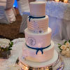 4 tier cake with groove-detailing and navy blue ribbons