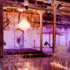 Rustic elegance with purple lighting, clear chairs, tea light lit aisle