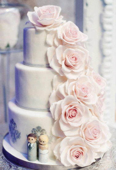 Simple three tier white cake with cascading pink roses and metallic stencil design