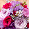 Vibrant summer bouquet with lavender, red and pink roses and accents.