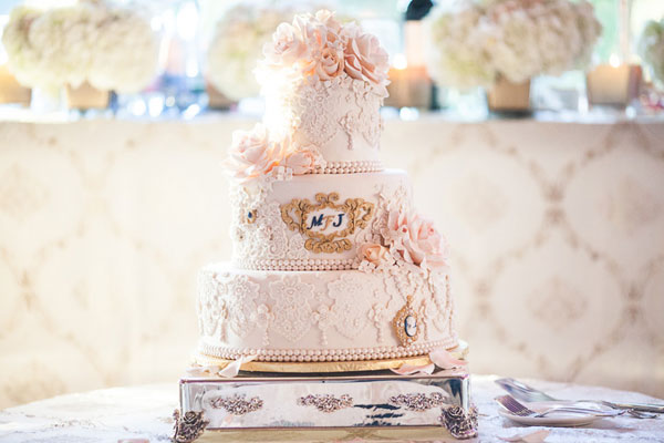 3 tier intricate white cake with lace detailing and soft pink roses