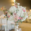 Rustic floral bouquet with twigs atop a slim silver stand